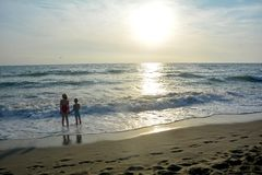 Boy and girl stand holding hands in the water on the beach Royalty Free Stock Photo