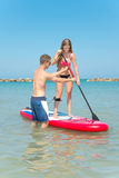 Boy and girl on stand up paddle Royalty Free Stock Image