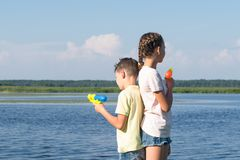 A boy and a girl are standing back to back and holding water pistols in their hands, playing in nature on vacation stock photography