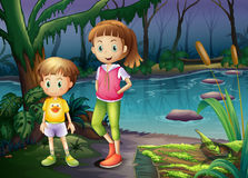 A boy and a girl standing in the middle of the forest Stock Image