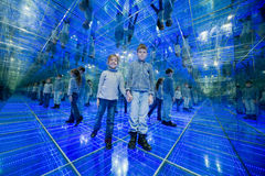 Boy and girl standing in a mirrored room Royalty Free Stock Photo