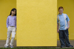 Boy (10-12) and girl (9-11) standing at opposite ends of yellow wall, smiling, front view, portrait Stock Photos