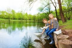 Boy, girl in striped shirts play with paper boats Royalty Free Stock Images