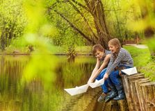 Boy and girl in striped shirts play paper boats Stock Photo