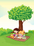 A boy and girl studying under tree Stock Image