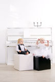 Boy and girl in a suit sitting on box Stock Photos
