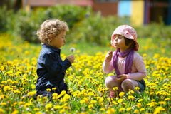 Boy and girl in summer flowers field Stock Photo