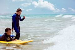 Boy and girl with surfboards in waving sea royalty free stock photography