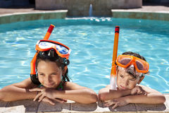 Boy & Girl In Swimming Pool with Goggles & Snorkel. A happy young boy and girl relaxing on the side of a swimming pool wearing orange goggles and snorkel Royalty Free Stock Photography