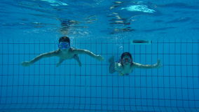 Boy and girl in swimming pool swim underwater stock footage