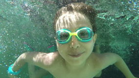Boy and girl swimming under water stock footage