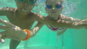 Boy and girl swimming under water stock video footage