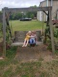 Boy and girl on swing stock image