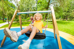Boy and girl swing in opposite directions Stock Images
