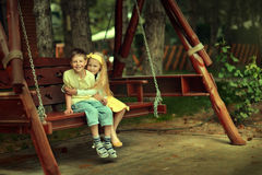Boy with the girl on a swing Stock Photography