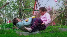 Boy and girl swinging in a hammock 4K stock video