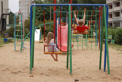 Boy with a girl swinging on a swing Royalty Free Stock Images