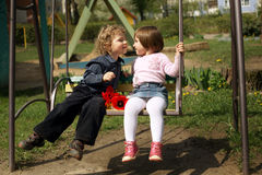 Boy and girl on the swings Royalty Free Stock Photo
