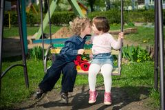 Boy and girl on the swings Stock Image