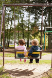 Boy and girl on the swings Royalty Free Stock Image