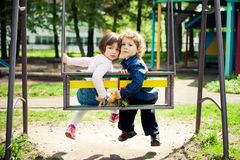 Boy and girl on the swings Stock Images