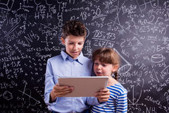 Boy and girl  with tablet against big blackboard, school Stock Photo