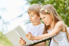Boy and girl with tablet in computer class. Boy and girl with tablet together make a computer course Royalty Free Stock Photo