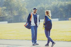 Boy and girl talking before workout. Young boy and girl before training talking in the stadium, preparing for workout Royalty Free Stock Images