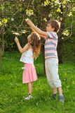 Boy and girl tear the tree flowers inside forest Stock Photos