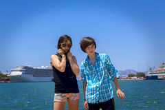 Boy and girl teenager on travel, ocean and big ships in backgrou Stock Images