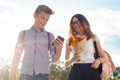 Boy and girl teenagers walking outdoor, couple smiling and talking. Sunny summer day, girl with bouquet of flowers royalty free stock photography