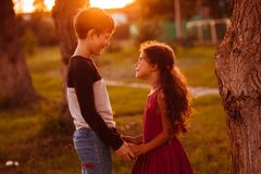 Boy girl teens are holding hands romance. Friendship love at sunset in summer sunlight outdoor areas Stock Photos
