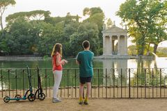 Boy and girl with their push scooters against the backdrop of the Tempio di Esculapio in the park Villa Borghese royalty free stock photos