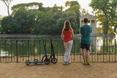 Boy and girl with their push scooters against the backdrop of the Tempio di Esculapio in the park Villa Borghese royalty free stock photo