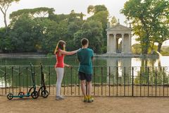 Boy and girl with their push scooters against the backdrop of the Tempio di Esculapio in the park Villa Borghese stock photo