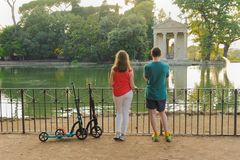 Boy and girl with their push scooters against the backdrop of the Tempio di Esculapio in the park Villa Borghese stock images
