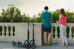 Boy and girl with their push scooters against the backdrop of the Vatican in the park Villa Borghese. stock photography