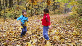 Boy and girl throwing up autumn leaves in the forest stock video
