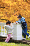 Boy and girl toddlers playing in autumn leaves Stock Image