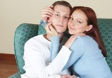 Boy and girl together 089. A young couple lovingly embracing on a couch stock images