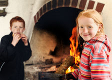Boy and girl together by the fireside Royalty Free Stock Photography