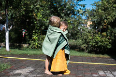 Boy and girl with a towel. Boy warms girl with a towel royalty free stock photo