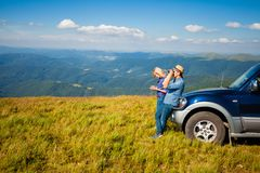 The tourists get lost during the trip. The boy and the girl are traveling in the mountains and navigating Stock Image