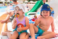 Boy and girl twins with lollipops. On summer holidays stock photography