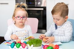 Boy and girl twins painting eggs for Easter. Morning royalty free stock photos