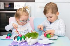 Boy and girl twins painting eggs for Easter. Morning stock photos