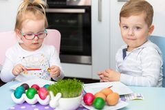 Boy and girl twins painting eggs for Easter. Morning royalty free stock photo