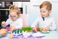Boy and girl twins painting eggs for Easter. Morning stock photography