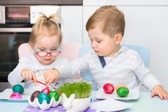 Boy and girl twins painting eggs for Easter. Morning stock image