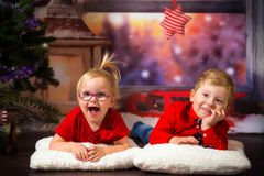 Twins posing in christmas scenery. Boy and girl twins posing in christmas scenery stock photo